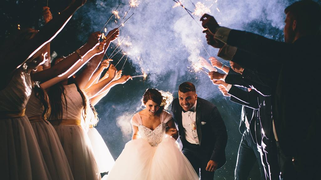 a bride and groom running under the held up arms of the wedding party holding sparklers